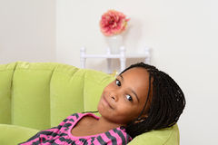 Young black child relaxing in green chair Stock Photography