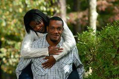 Young Black couple. Young Black or African-American couple outside. Woman playfully riding on man's back royalty free stock image