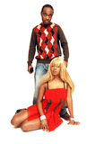 Young black couple 93. Young African American couple, she is sitting on the floor and he is standing Stock Photography