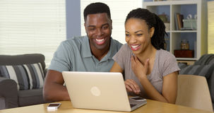 Young black couple browsing internet on laptop together. In the living room royalty free stock photo