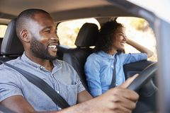 Young black couple in car on a road trip look ahead smiling Stock Photography