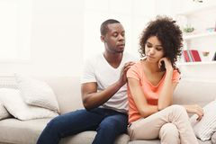 Young black couple making peace after quarreling at home. Young african-american couple making peace after quarreling at home, women still feeling offended Stock Images