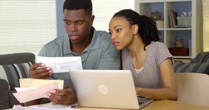 Young black couple paying bills online with laptop computer. Serious young black couple paying bills online with laptop computer Stock Photography
