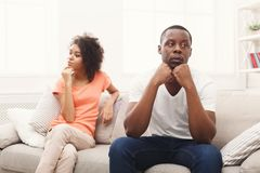 Young black couple quarreling at home. Young african-american couple quarreling at home, offended at each other . Family relationship difficulties concept Stock Images