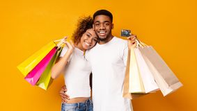 Young black couple with shopping bags and credit card. Consumerism and relationship concept. Happy black couple with shopping bags and credit card, orange royalty free stock photo