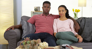 Young black couple sitting on couch looking at camera Royalty Free Stock Photo