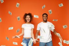 Young black couple standing under money banknotes shower. Financial success. Excited young african-american couple standing under money banknotes shower, orange stock images