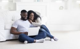 Young black couple using laptop at home planning summer vacation