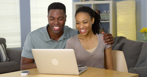 Young black couple watching funny video on laptop Stock Photos