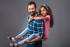 Young black dad with his daughter. A young black men standing and caring his daughter on his backr Royalty Free Stock Photo
