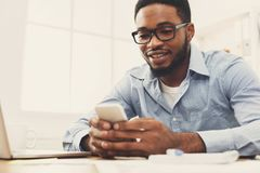 Young black businessman using mobile phone. Young black employee at workplace using mobile phone, checking social media on smartphone, taking break, copy space Royalty Free Stock Photo