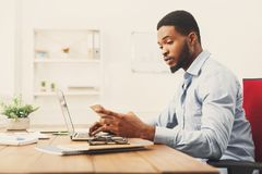 Young black businessman using mobile phone. Young black employee at workplace using mobile phone, checking social media on smartphone, taking break, copy space Stock Photo