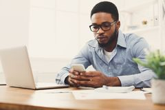 Young black businessman using mobile phone. Young black employee at workplace using mobile phone, checking social media on smartphone, taking break, copy space Royalty Free Stock Images