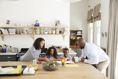 Young black family busy together in their kitchen stock photography