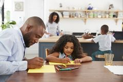 Young black family of four busy in their kitchen, close up stock image