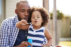 Young black father and daughter blowing bubbles outside stock images