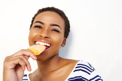 Young black female eating ice cream against white wall Stock Photos