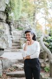 Young black female person standing near rock and stone stairs in park, having ponytail. Young black female person standing near rock and stone stairs in park Stock Photography