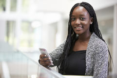 Young black female student holding phone in university foyer Royalty Free Stock Photos
