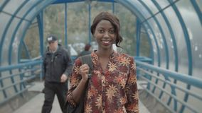 Young black female teacher with afro hairstyle wearing small leather jacket briefcase, walking out from office building. Young black female teacher with afro stock video footage