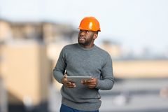 Young black foreman checking the object. Stock Images