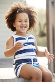 Young black girl blowing bubbles outside her home royalty free stock images