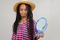 Young Black girl looking in mirror Royalty Free Stock Photo