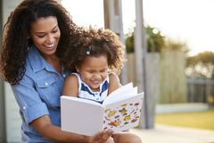 Young black girl reading book sitting on mum�s knee outdoors stock photos