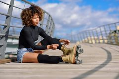 Free Young Black Girl Sitting On Urban Bridge And Puts On Skates. Woman With Afro Hairstyle Rollerblading On Sunny Day Stock Photos - 131810603