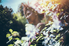Young black girl surrounded by wild flowers. True tilt-shift view of young cute black female teenager with chamomile wreath on her head with curly afro hair Royalty Free Stock Photos