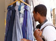 Young black guy looking at clothes outside. Portrait of a young black guy looking at clothes outside Royalty Free Stock Images