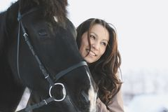 Young black hair woman hugging a horse - portrait. Close up Royalty Free Stock Photo