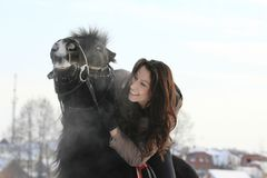 Young black hair woman hugging a horse - portrait. Close up Stock Photography