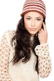Young black hair woman in wool sweater and cap. On white Stock Image