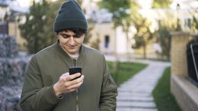 Young black haired guy texting in a park. Close up of a young man wearing a dark green vest and a beanie standing in a park and texting from his phone. Locked stock footage