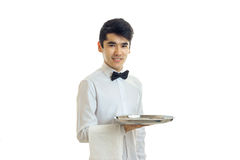 A young black-haired waiter in a white shirt smiling and holding a tray Royalty Free Stock Photos