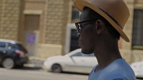 Young black hipster man walks through the city stock video