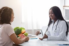 Woman nutritionist using digital tablet in office, consulting patient