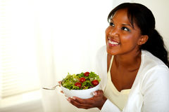 Young black lady looking up and holding a salad. Portrait of a pretty young black lady looking up and smiling while holding a salad. With copyspace Royalty Free Stock Image