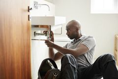 Young black male plumber sitting on the floor fixing a bathroom sink, seen from doorway stock photos