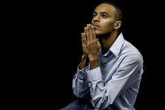 Young black male praying. Nice isolation of a young african american black male praying with plenty of space for custom text Stock Photo