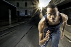 Young black male running in an urban setting. Horizontal shot of black african american male running, urban setting with sun flare, motion blur, shows spped and Royalty Free Stock Image