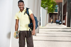 Young Black Male With Skateboard and Bag Royalty Free Stock Images