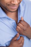 Young black male unbuttons shirt. Royalty Free Stock Image