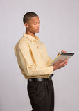 Young Black Male Writing on Notepad Stock Photo