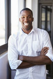 Young black man with arms crossed smiling, vertical portrait Stock Images