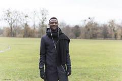 Young Black Man in Autumn Coat Posing in Park