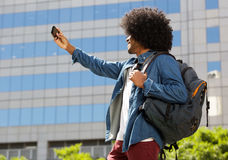 Young black man with bag taking selfie Royalty Free Stock Photography