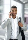 Young black man with bag talking on mobile phone Stock Photography