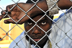 Young black man behind a fence. Attractive African American young man portraying sadness and depression while leaning against a chain link fence Stock Photos